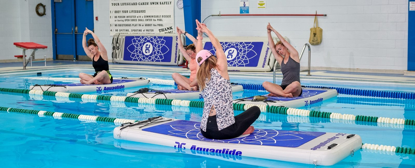 People sitting on floating boards in the pool doing yoga